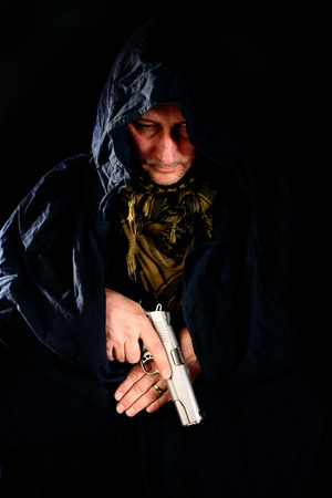 45 gun: man in hood holding a pistol over black