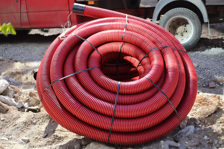 plastic conduit: Red colored plastic tube coils on construction site