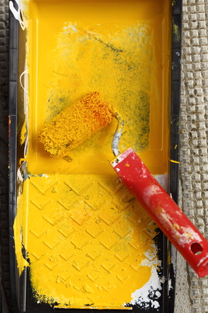 yellow paint: a paint roller of workplace, close up Stock Photo