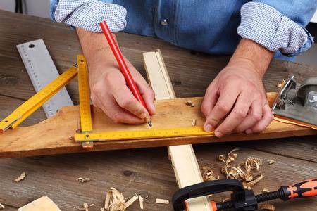 yardstick: carpenter hand with yardstick and pencil