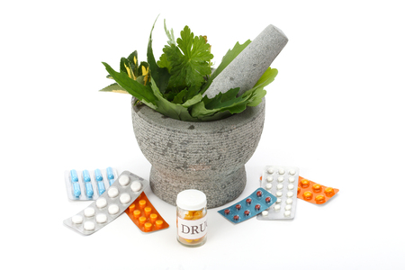 mortar and pestle: Mortar, pestle, herbs and pills over white.