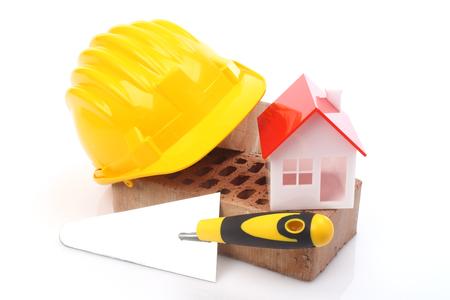 materiales de construccion: Ladrillos, paleta y un casco sobre blanco
