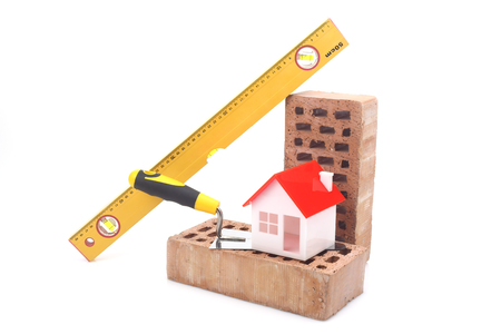 construction material: Bricks, trowel and level over white
