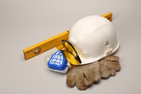 safety goggles: Safety gear kit close up over grey Stock Photo