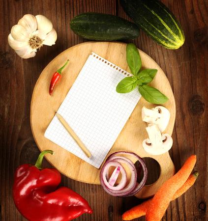 menu background: Fresh vegetables and blank recipe book