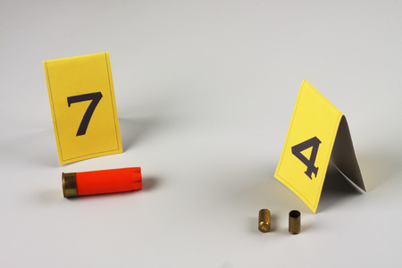 bullet proof: shotgun shell marked as evidence on grey