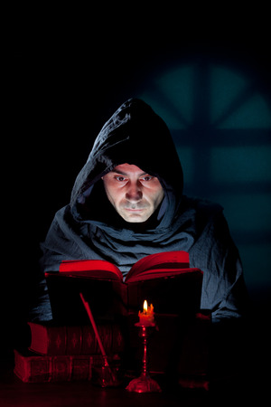 occult: A Monk read mystical occult book in the dark