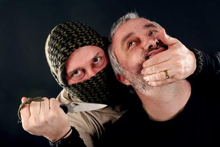 een gemaskerde man met een mes aangevallen andere man Stockfoto