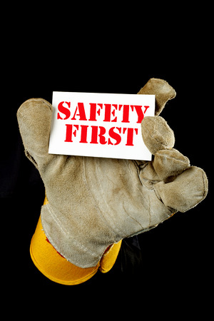 safety first: worker holding a card  with the inscription SAFETY FIRST Stock Photo