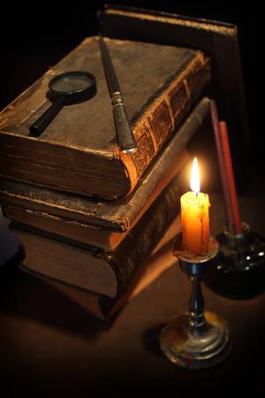 pluma de escribir antigua: Pila de los libros antiguos y una vela