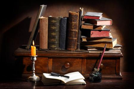Stapel der alten Bücher und eine Lupe