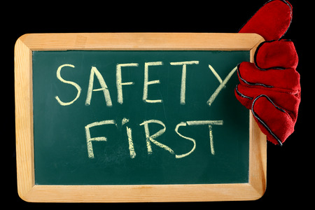 safety first: worker holding a board with the inscription SAFETY FIRST Stock Photo
