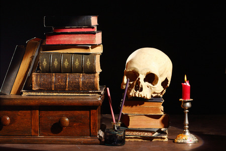 macbeth: old books and skull over black Stock Photo