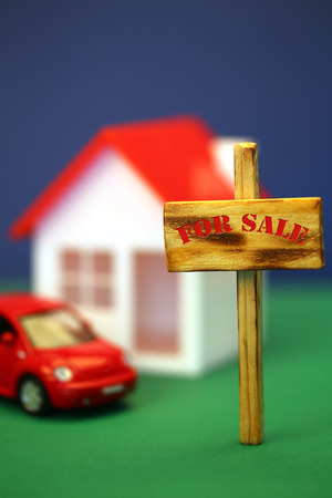 home for sale sign: Home for sale sign in front of house model, shallow field of focus Stock Photo