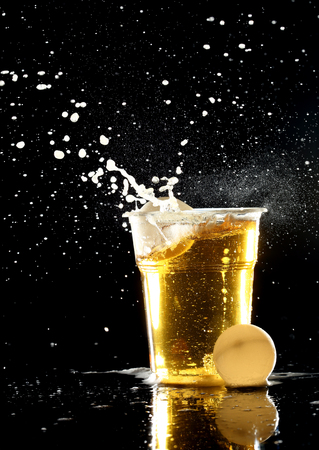 beer and ping pong balls over black