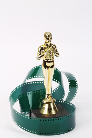 Movie award and film tape over white