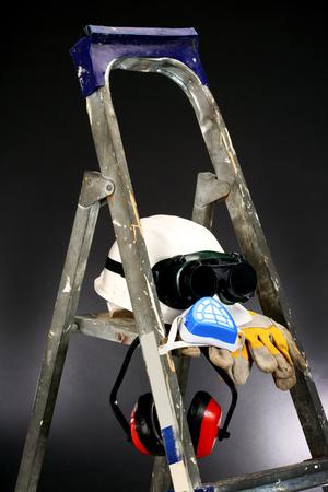 Safety gear kit on step ladder over black