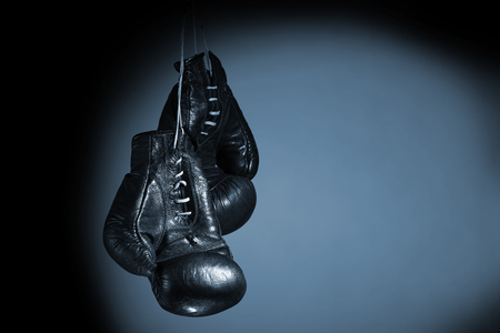 Old boxing gloves hanging close up