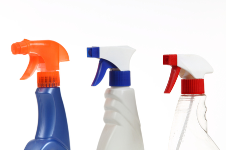 different cleaning spray bottles on white