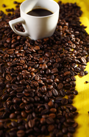 Coffee beans and a cup of coffee, selective focus