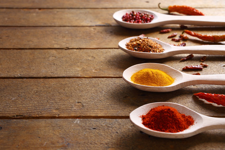 Spices in wooden spoons, close up, shallow dof