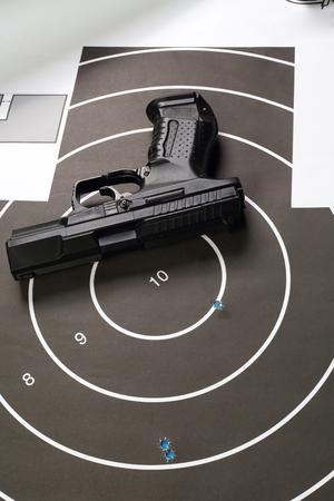 black pistol on paper target