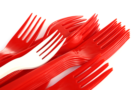 pile of red plastic forks and one white Imagens