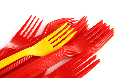 pile of red plastic forks and one yellow Imagens