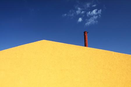 an abstract yellow facade and blue sky