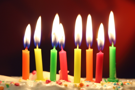 eight lit birthday candles close up shallow dof stock photo