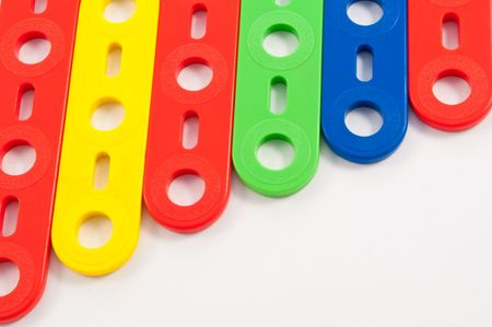 nursery school: Close up of a selection of brightly coloured construction toys arranged parallel over white. Stock Photo