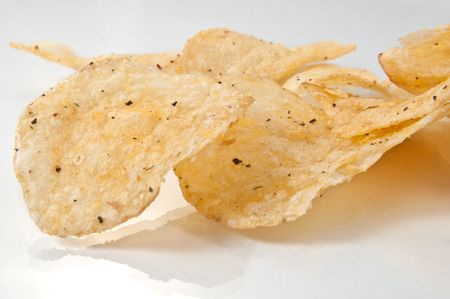 Close up of a group of potato crisps arranged on a white reflective surface with white background. Stock Photo - 6600932
