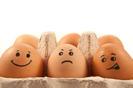 Close and low level capturing a group of brown eggs with painted faces arranged in carton with white background. photo