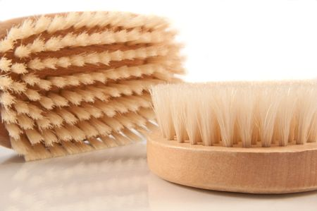 Close and low level capturing two wooden soft brushes used for body brushing and spa. Arranged over white.