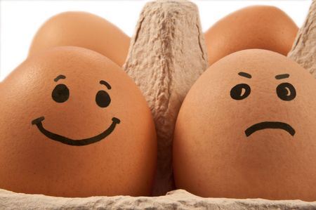 capturing: Close and low level capturing two eggs with painted faces arranged in carton against white background