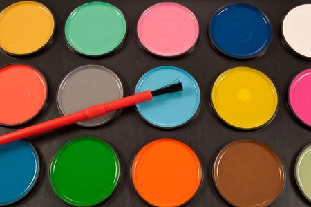 Close up of many dry, round, coloured watercolour paint tablets arranged over black with paintbrush. photo