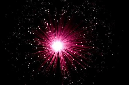 fibre optic: Overhead view capturing an illuminated red fibre optic light display arranged over black. Stock Photo