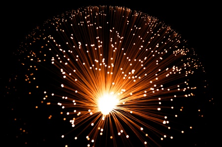 Overhead view capturing a golden illuminated fibre optic lamp against black. photo