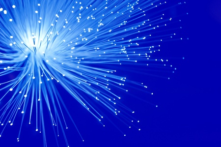 Close up capturing illuminated blue fibre optic light strands against a vibrant blue background. photo