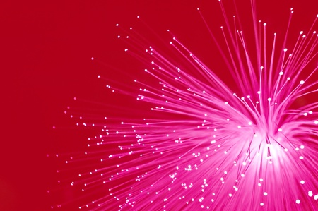 Abstract style close up capturing bright pink illuminated fibre optic light strands against a bright red background. Stock Photo - 8438530