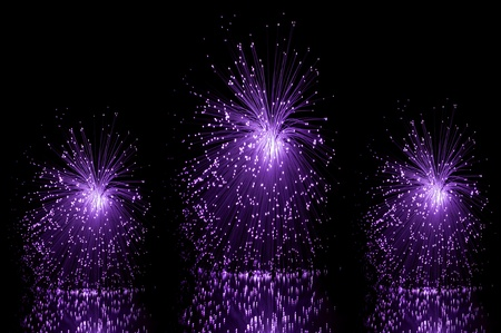 Low level angle capturing three violet groups of illuminated fibre optic light strands against a black background and reflecting into the foreground. photo