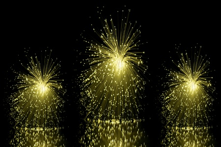 Low level angle capturing three yellow groups of illuminated fibre optic light strands against a black background and reflecting into the foreground. Stock Photo - 8613256