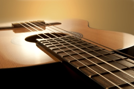 guitar: Close and low level angle capturing an acoustic guitar with warm brown background. Focus on foreground strings.