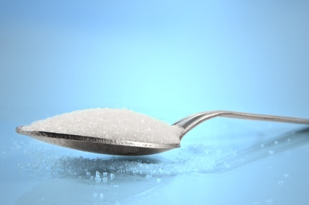 granular: Close and low level capturing a tea spoon with sugar granules against a blue background.