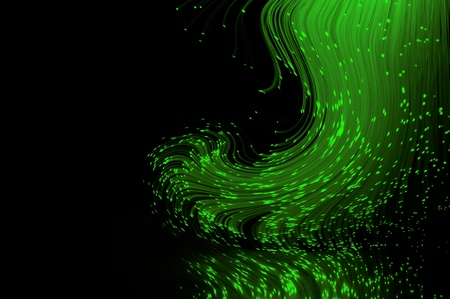 emerald: Bright green fiber optic light strands swirling against a black background and reflecting into the foreground. Stock Photo