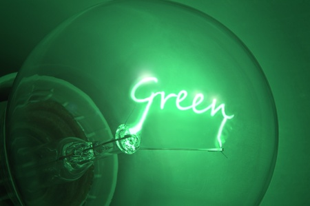 energy saving: Close up of green light bulb with the illuminated filament spelling the word Green