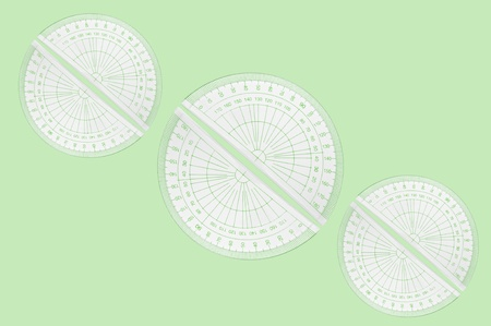 millimetres: Several plastic protractors arranged in formation over pale green background. Stock Photo