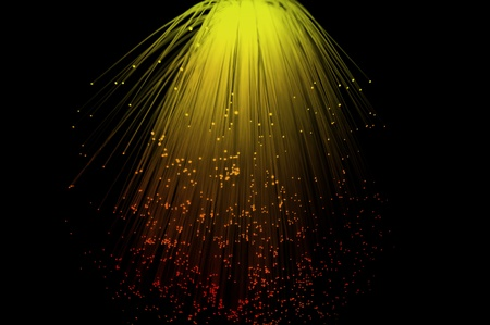 Yello and red coloured fibre optic light strands cascading down with a black background. photo