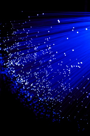 Close up on ends of many illuminated deep blue fibre optic strands with black background. photo