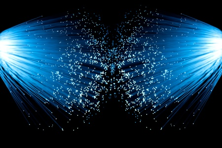 Two illuminated groups of blue fibre optic strands emanating from the left and right of the image. Black background. Stock Photo - 8807859